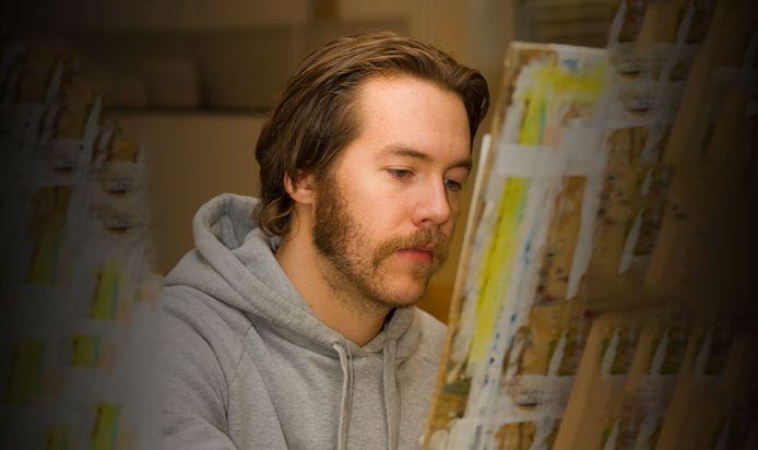 An artist is focusing on his artwork