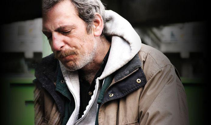 A homeless man looking sad
