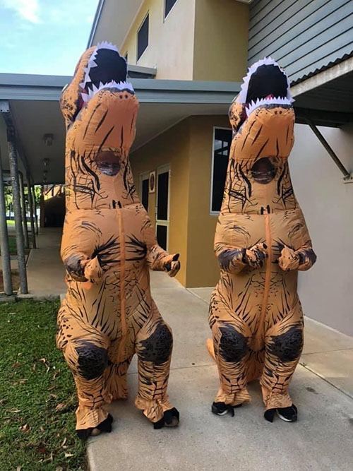 TRex costumes welcoming people