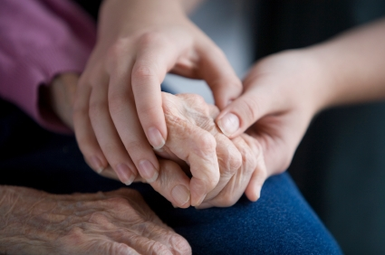 older person holding hands with a younger person