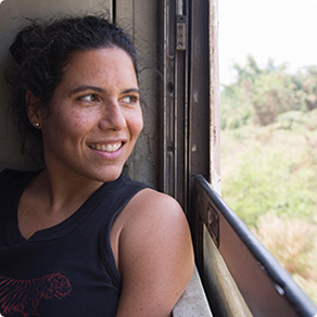 A woman smiling and looking outside of a moving train