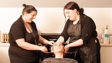 Two hairdressers with a client